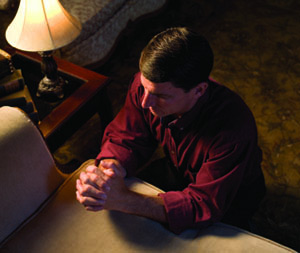 A man kneeling at his couch and praying.