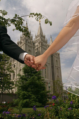 A couple holding hands in front of the Salt Lake City temple.